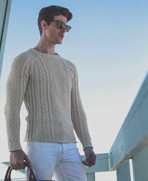 Mann in weißer Jeans und hellem Strickpullover auf Jacht