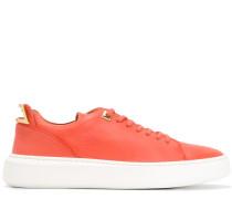 Sneakers mit goldfarbenen Beschlägen