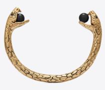 Armreif mit Schlangenanhänger aus goldfarbenem Metall mit schwarzen Glasperlen.