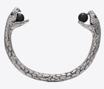 Armreif mit Schlangenanhänger aus silberfarbenem Metall mit schwarzen Glasperlen.