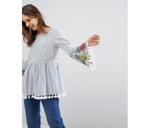 Gestreifte Bluse mit bestickten Ärmeln und Bommel-Besatz