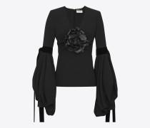 Top mit tiefem V-Ausschnitt, Oversize-Ärmeln aus schwarzem Sablégewebe und schwarzer Lederblume