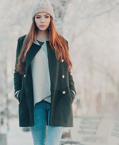 Frau mit Mantel und Strickmütze in winterlicher Landschaft