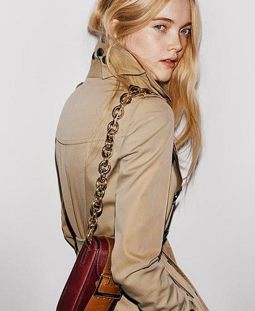 Frau mit beigem Burberry-Trenchcoat und Tasche